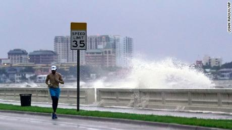 A jogger runs Wednesday in Tampa as a wave breaks over a seawall.